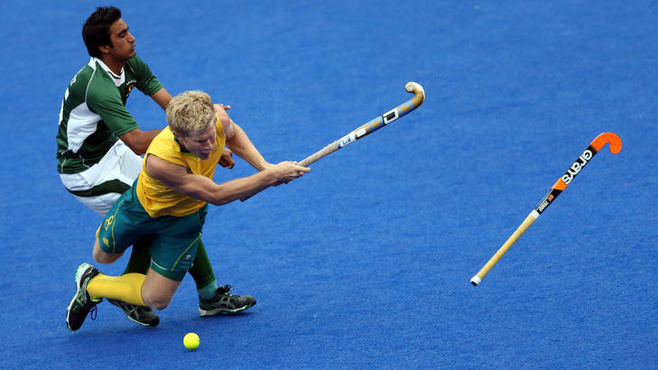 Matthew Butturini of Australia is fouled by Shafqat Easool of Pakistan during their men's hockey preliminary match at the London Olympics.